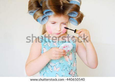 Adorable funny little girl making makeup with mother cosmetics