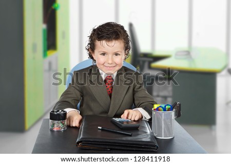 Adorable future businessman in the office - stock photo