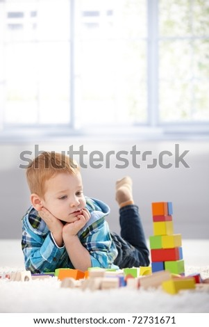 Adorable gingerish little boy laying on floor, playing with building cubes.? - stock photo