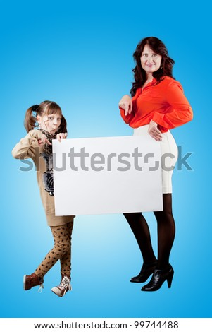 adorable girl and mother holding blank billboard on blue background. - stock photo