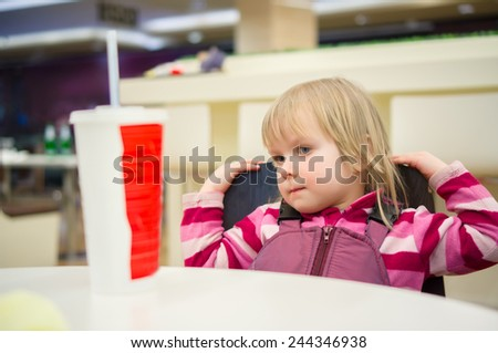 Adorable girl and soda on table in fast food restaurant - stock photo