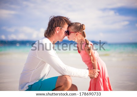 Adorable girl and young dad have fun on white beach