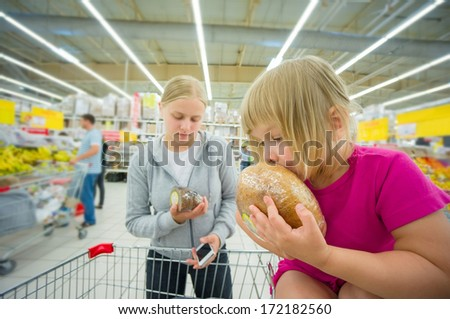 Adorable girl at shopping cart  and mother select products in supermarket - stock photo
