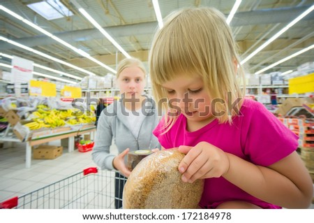 Adorable girl at shopping cart  and mother select products in supermarket