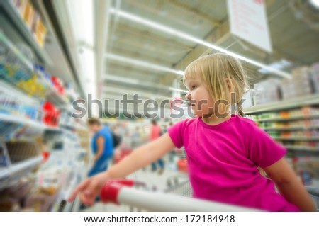 Adorable girl at shopping cart select products in supermarket