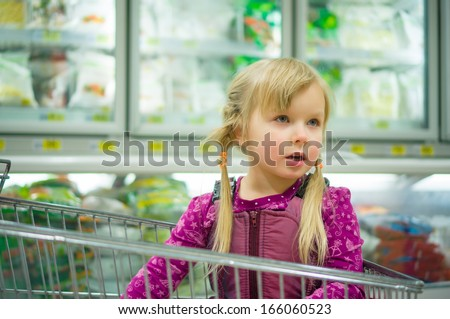 Adorable girl at shopping cart with frozen food in fridges on back
