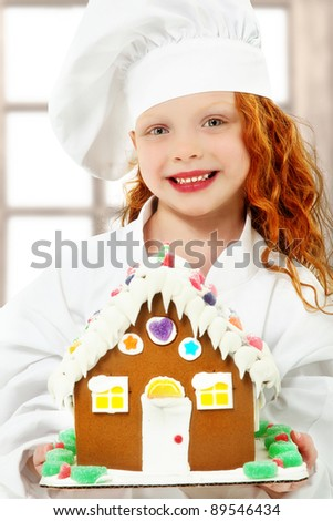 Adorable girl child in chef uniform holding a ginger bread, gingerbread house over white background.