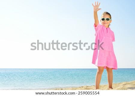 Adorable girl dancing on the beach - stock photo