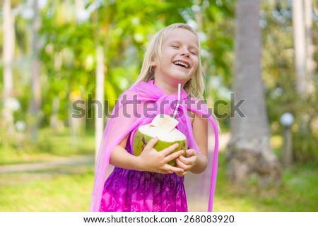 Adorable girl drink coconut milk on tropical island - stock photo