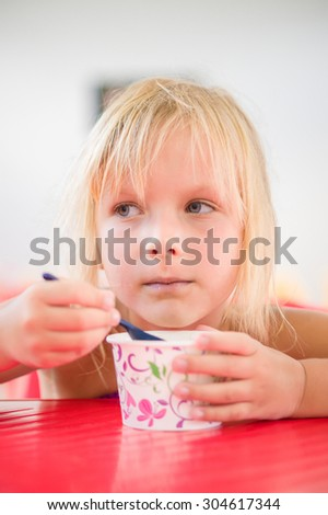 Adorable girl eat chocolate ice cream in cup with spoon in cafe