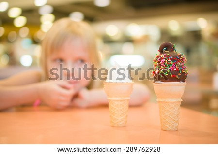 Adorable girl eat chocolate ice cream with sprinkles in mall