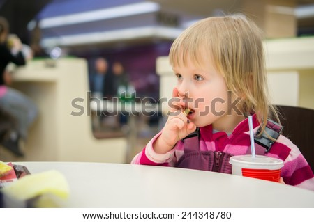 Adorable girl eat potato in fast food restaurant - stock photo