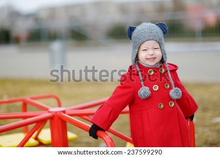 Adorable girl having fun on a playgroud on beautiful spring day - stock photo