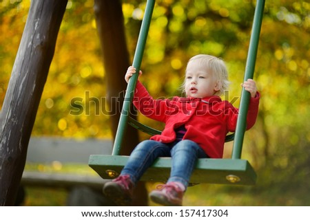 Adorable girl having fun on a swing on autumn day