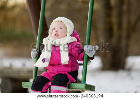 Adorable girl having fun on a swing on beautiful winter day - stock photo