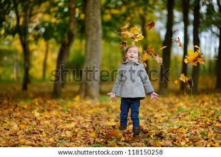 Adorable girl having fun on beautiful autumn day