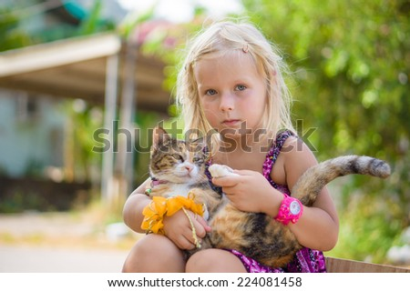 Adorable girl hold cute cat on backyard - stock photo
