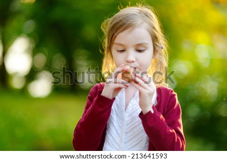 Adorable girl holding clay whistle in her hands