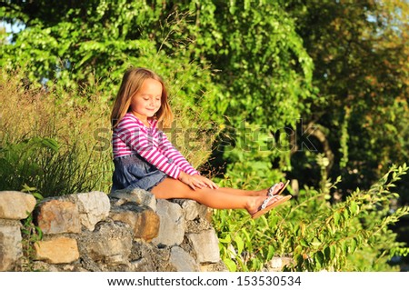 adorable girl in a stripe dress sitting on rocks in a park - stock photo