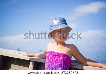 Adorable girl in blue hat on longtail boat in open ocean near islands - stock photo
