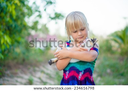 Adorable girl in color dress hold small kitten on hands