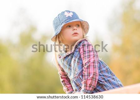Adorable girl in dress and hat climb on constructions on playground - stock photo