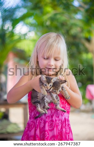 Adorable girl in pink color dress holds small kittens in hands