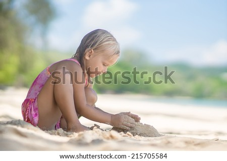 Adorable girl in pink swimming suit play on beach making sand tower - stock photo
