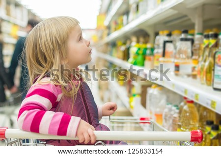 Adorable girl in shopping cart selecting sunflower oil in supermarket
