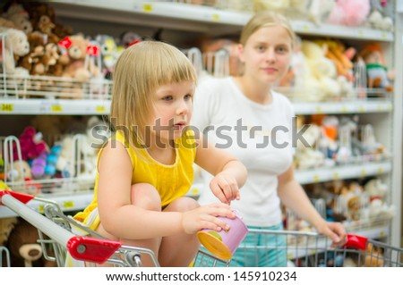 Adorable girl in shopping cart with mother on back select toys in supermarket