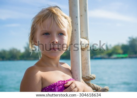 Adorable girl look to the sea on side of ferry ship deck - stock photo