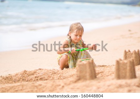Adorable girl make sand castle on beach - stock photo