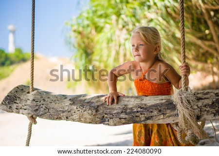 Adorable girl near rope swing under palm trees on tropical island - stock photo