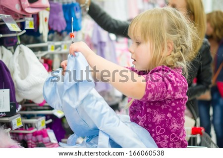 Adorable girl on shopping cart select blue dress in supermarket
