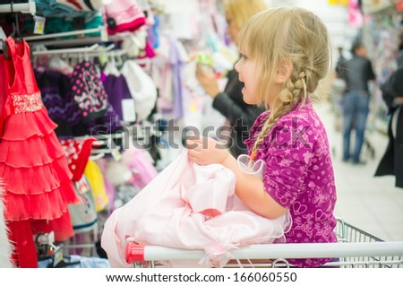Adorable girl on shopping cart select pink dress in supermarket