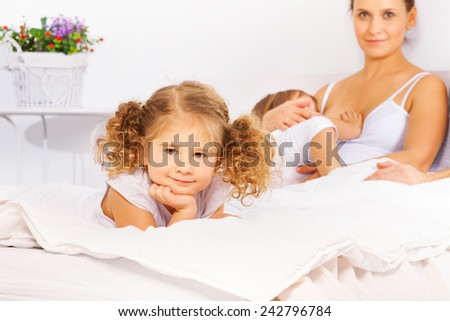 Adorable girl on white bed with mother feeding son - stock photo