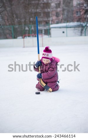 Adorable girl play with hockey stick in skates  on ice rink - stock photo