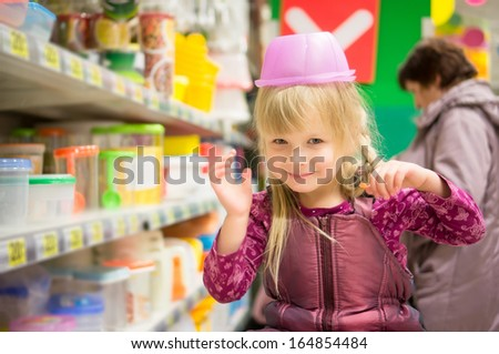Adorable girl play with plastic containers on head in supermarket - stock photo