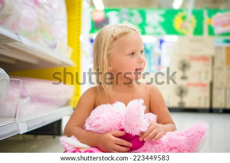 Adorable girl play with plush toy and pillow sitting on floor in department section