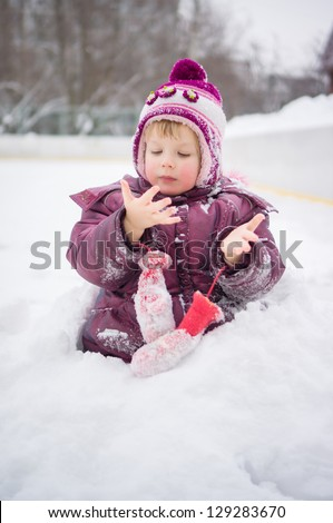 Adorable girl play with snow without mittens on ice rink - stock photo