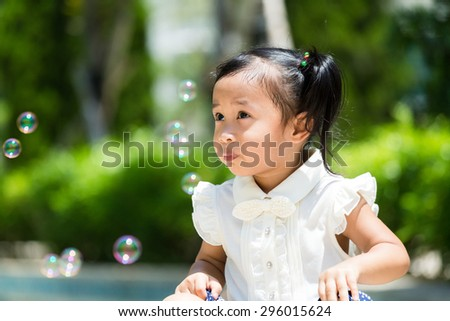 Adorable girl playing bubble blower at outdoor - stock photo