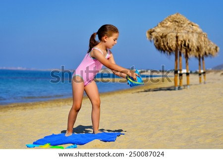 Adorable girl playing with her toys at beach - stock photo