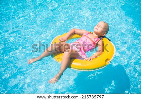 Adorable girl relax on yellow life ring in pool at tropical beach resort