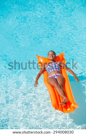 Adorable girl relaxing at the swimming pool