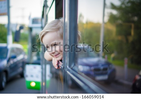Adorable girl ride by bus and look through open window. Outside shoot - stock photo