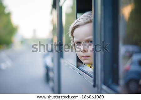 Adorable girl ride by bus and look through open window. Outside shoot