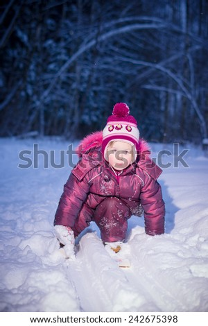 Adorable girl ride on ski in evening park