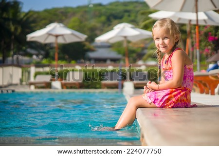 Adorable girl seat at side of swimming pool with legs splashing at tropical beach resort. Chairs and umbrellas on back - stock photo