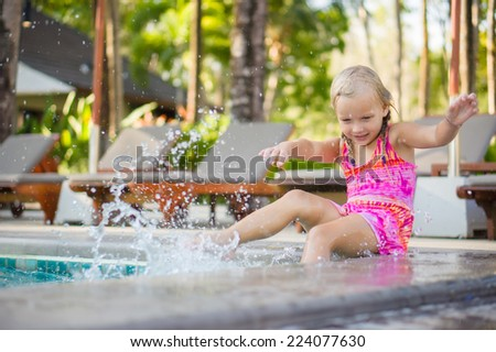 Adorable girl seat on  pool side at tropical beach splash water with legs. Chairs and umbrellas on back - stock photo
