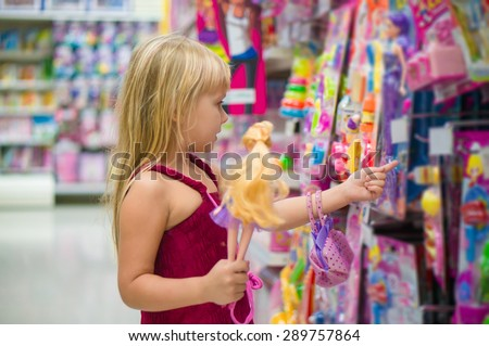 Adorable girl select dolls in toy section of supermarket